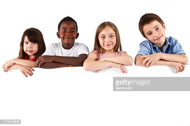 Group of multi ethnic children holding a white board