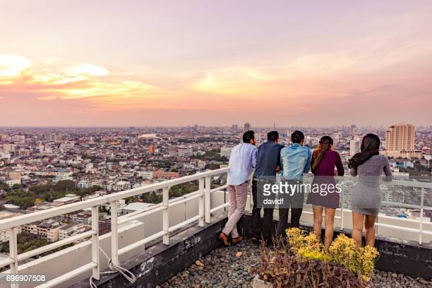 Group of Multi Ethnic Friends Enjoying Rooftop Sunset Drinks