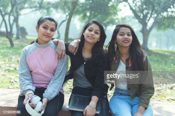 group of multi ethnic happy female friends sitting on a bench in the park and enjoying in nature. - simple living stock pictures, royalty-free photos & images