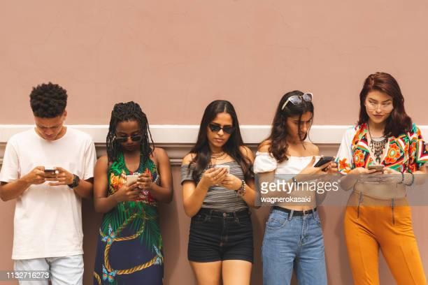 groep van multi-etnische latijns-tieners met behulp van smartphone buitenshuis - verslaving stockfoto's en -beelden