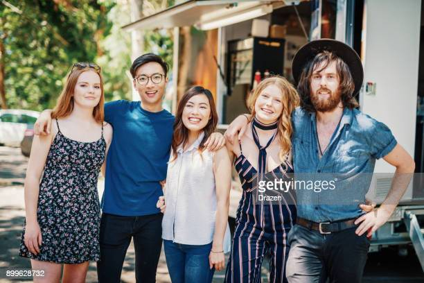 group of multi ethnic people posing near the food truck after delicious meal - korean teen stock pictures, royalty-free photos & images