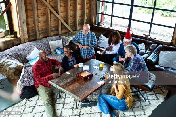 group of multi racial friends playing games and chatting at christmas - ゲスト ストックフォトと画像