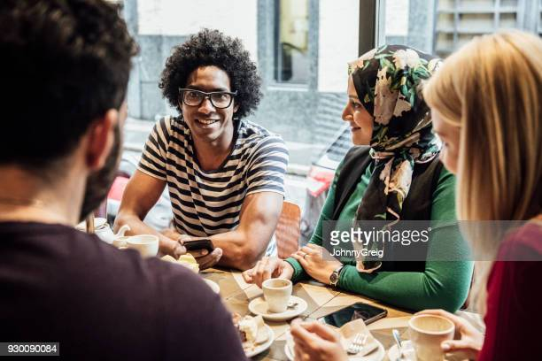Group of multi racial friends sitting in cafe with food and drink talking and smiling