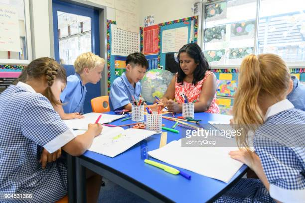 Group of multi racial school children in classroom with their teacher