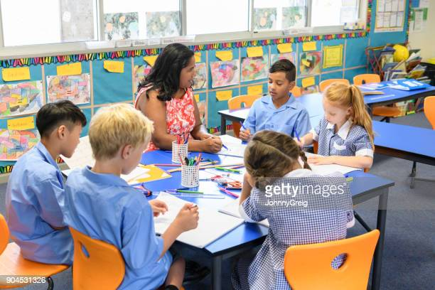 Group of multi racial school children working around a table with their teacher