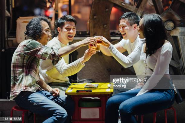 group of multi-ethic travelers enjoying at japanese pub - japanese culture stock pictures, royalty-free photos & images