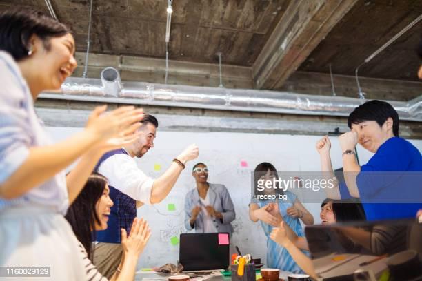 ビジネスの成功を祝う多民族ビジネスの人々のグループ - 拍手喝采 ストックフォトと画像