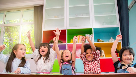Group of multi-ethnic five little kids children African American, asian and Caucasian happiness together with friend to draw colour pencil to full colour of picture in living room or class room 1133921273