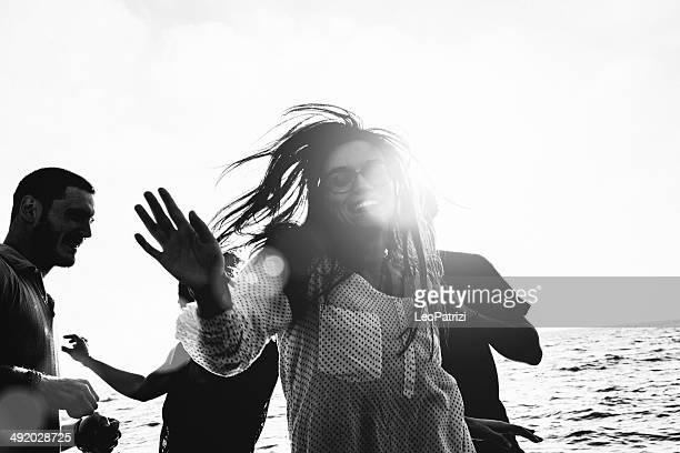 Grupo multiétnico de amigos bailando en la playa