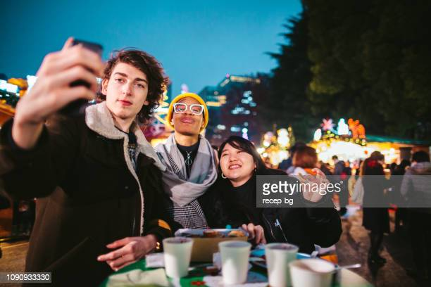 Group of multi-ethnic friends enjoying eating street food at street market