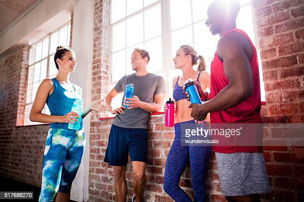 Group of multi-ethnic friends recovering and hydrating at the gym