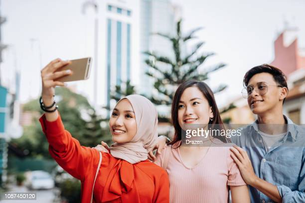 group of multi-ethnic friends taking selfie for social networks in asia - social media marketing stock pictures, royalty-free photos & images