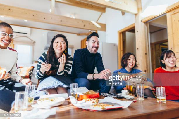 group of multi-ethnic friends watching movies with beer and pizza at home party - adult video japan stock pictures, royalty-free photos & images