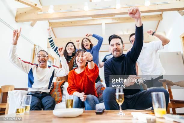 ビールとピザ ホーム パーティーでテレビを見ている多民族の友人のグループ - 応援 ストックフォトと画像