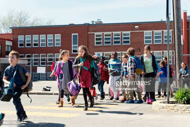 group of multi-ethnic kids crossing street getting out school. - quebec stock pictures, royalty-free photos & images