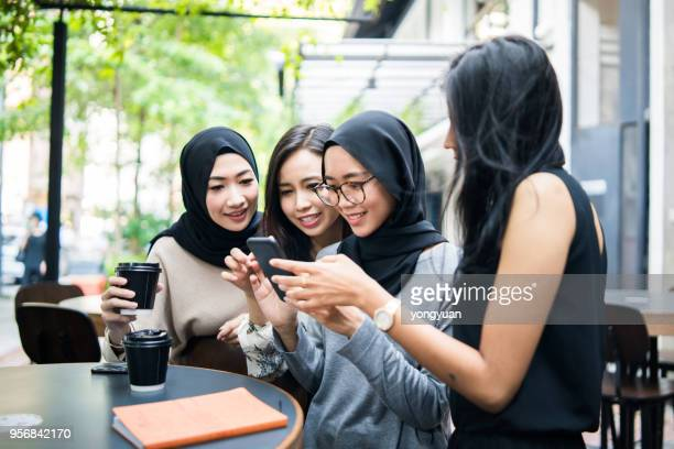 group of multi-ethnic malaysian girls looking at a smartphone - malaysia beautiful girl stock photos and pictures
