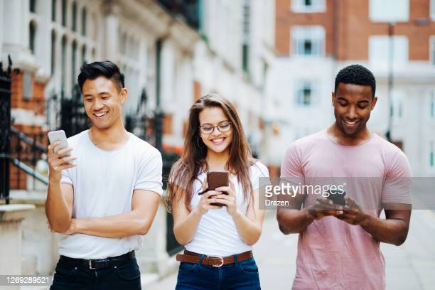 group of multi-ethnic millennial friends outdoors in summer in city, youth using phones for video calls and texting - season 3 stock pictures, royalty-free photos & images