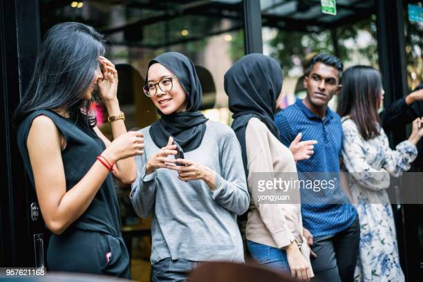 group of multi-ethnic people having a talk - malaysia beautiful girl stock photos and pictures