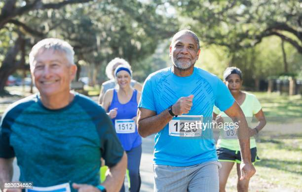 group of multi-ethnic seniors running a race - spring racing stock photos and pictures