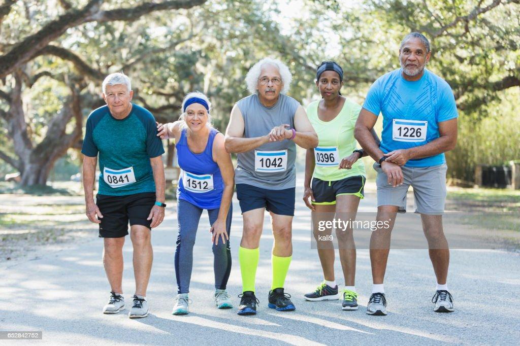 Grupp av multietnisk seniorer inställd på att köras i ett lopp : Bildbanksbilder