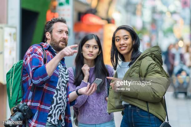 多民族観光の友人のグループは、方向のためのスマートフォンをチェック - 観光客 ストックフォトと画像