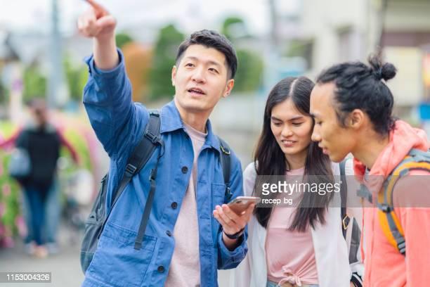 多民族観光の友人のグループは、方向のためのスマートフォンをチェック - 多民族 ストックフォトと画像