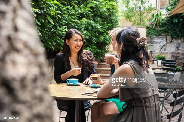 group of multi-ethnic women drinking and chilling in a cafe in sydney - north stock pictures, royalty-free photos & images