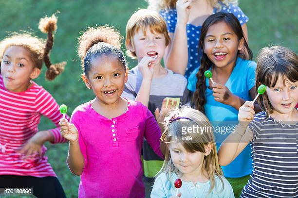 Group of multiracial children eating lollipops