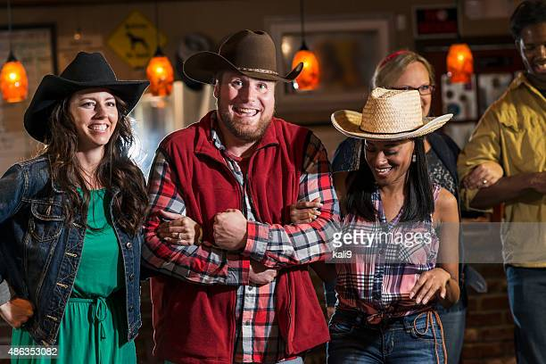Group of multiracial friends dancing in cowboy hats