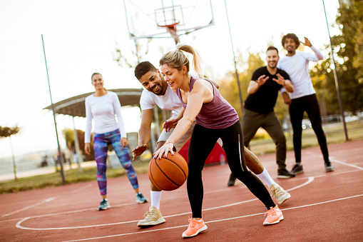 Group of multiracial young people   playing basketball outdoors 1062855462