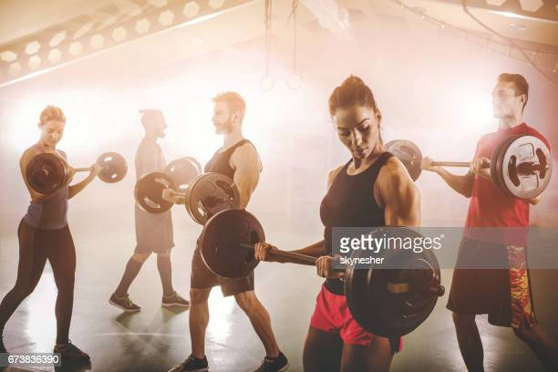 Group of muscular build athletes exercising with barbells.