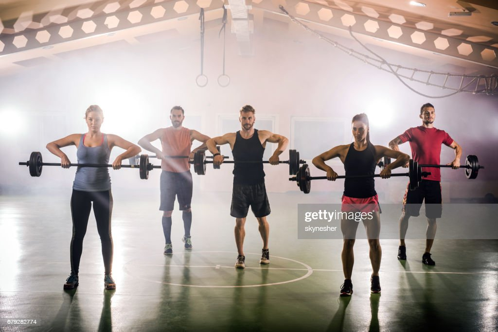 Group of muscular build athletes having a weight training in gym. : Stock Photo