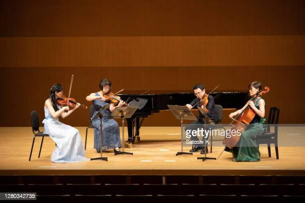 group of musicians playing instruments at classical concert - classical musician stock pictures, royalty-free photos & images