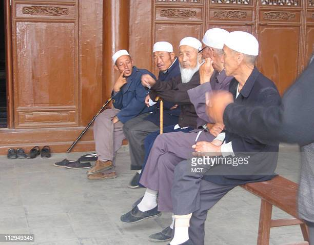 A group of Muslim ethnic Hui minority laypeople rest outside the Tongxin Mosque in a city of the same name in northwest China Many young Hui are...