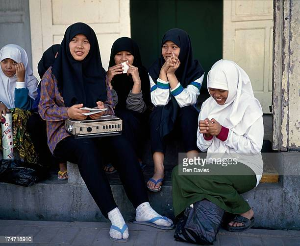 MOSQUE SURAKARTA JAVA INDONESIA A group of Muslim girls dressed in headscarfs relax in a doorway near the Grand Mosque in Surakarta Indonesia is home...