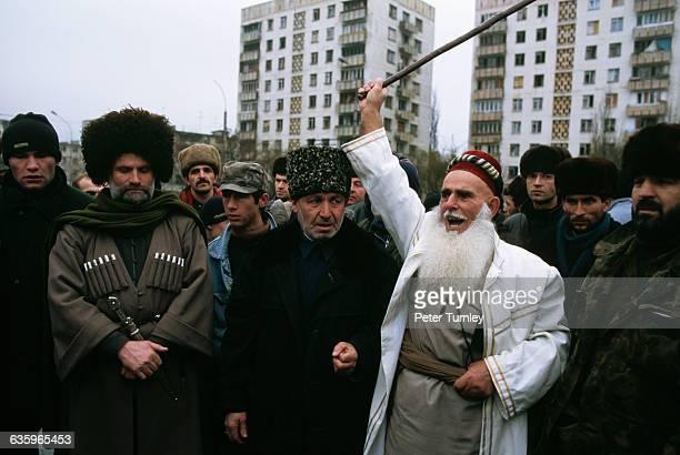 A group of Muslim men listen to an elderly Muslim man shout