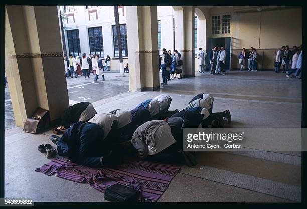 Group of Muslim students pray in a courtyard at Delacroix High School in Algiers.
