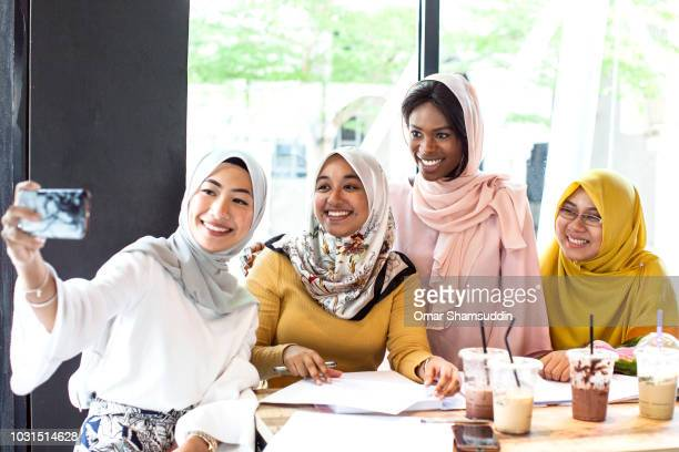 A group of muslim university students taking a selfie