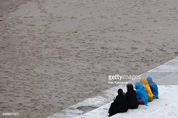 A group of muslim women sit at beach in Wudam Al Sahil, Oman