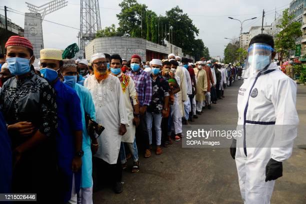 Group of Muslims queue with no social distance at the Baitul Mukarram National Mosque for Eid Al-Fitr prayers amid Coronavirus crisis. Eid Al-Fitr...