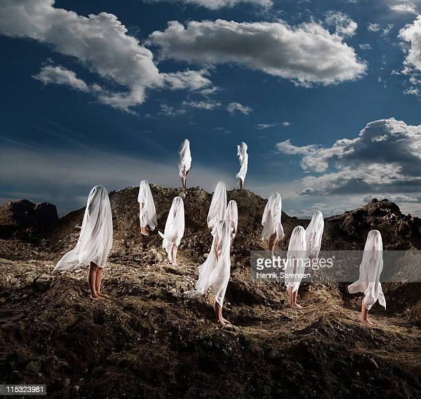 group of naked people covered with white linnen