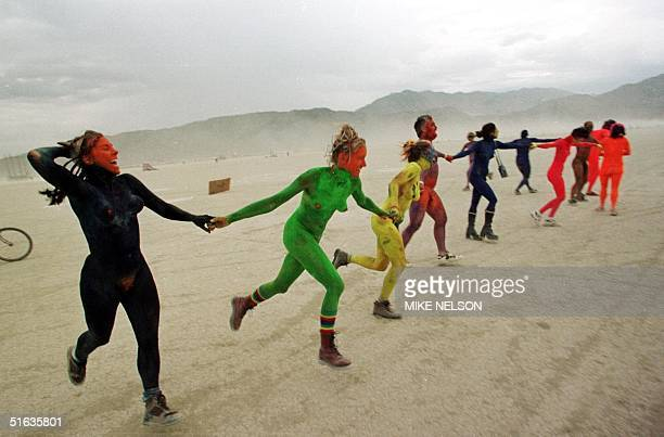 A group of naked people painted in various colors run through the Black Rock Desert in Nevada 06 September as part of the 'Burning Man' festival...