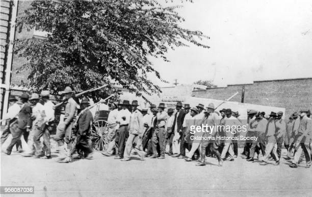 Photograph of a group of National Guard Troops who are carrying rifles with bayonets attached while escorting unarmed African American men after the...