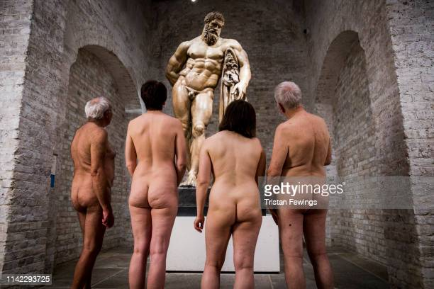 Group of naturists admire a nude cast of Hercules during a private event at Royal Academy of Arts in May in London, England.