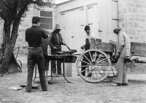 A group of Navajo Indian men are blacksmithing at Hunter's Point day school to repair a broken wagon early to mid 20th century