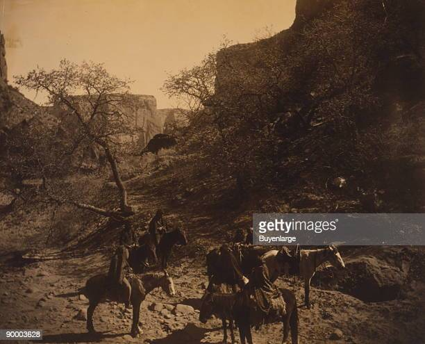 Group of Navajos most on horseback pause at the bottom of a rocky canyon