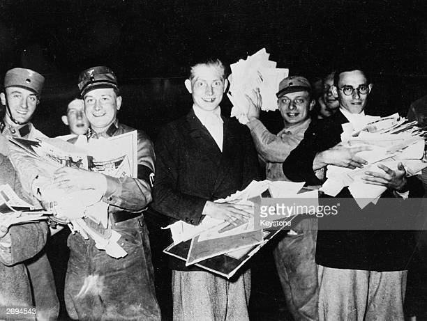 A group of Nazi troops and students gather seized papers and books to burn in the Opernplatz Berlin