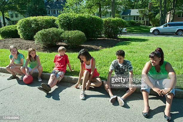 Group of Neighborhood Kids sitting on Curb