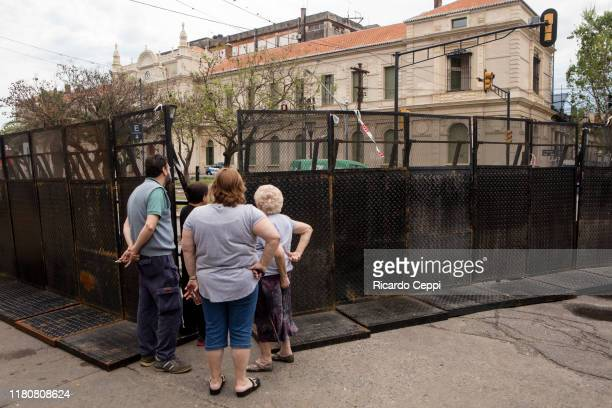 A group of neighbors look at the building where the first session of the Argentine presidential debate will take place tonight at Universidad...