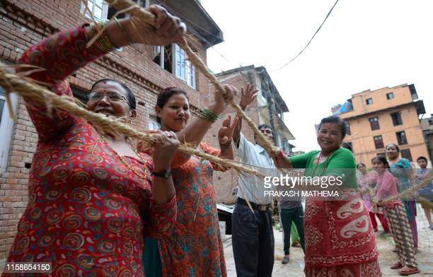 TOPSHOT A group of Nepali people make a straw effigy of Ghanta Karna during celebrations of the Hindu festival of Gathemangal also known as Ghanta...